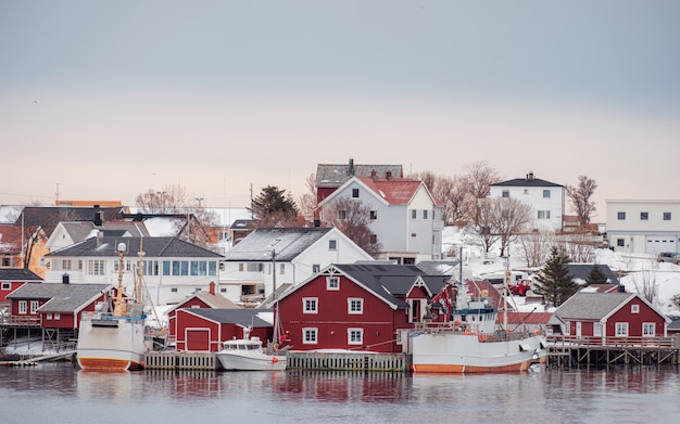 Village norvégien avec bateau de pêche sur le littoral en hiver Photo Premium