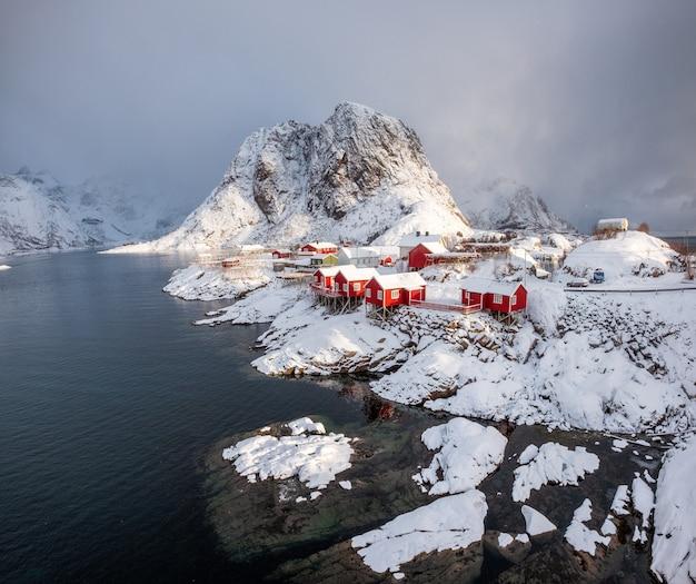 Village de pêcheurs de maison rouge avec montagne de neige au jour de la neige Photo Premium