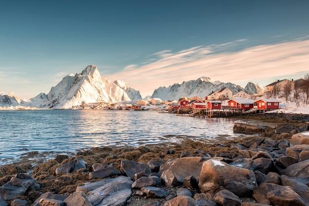 Village de pêcheurs scandinave avec montagne enneigée au littoral Photo Premium