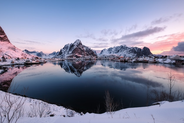 Village scandinave enneigé avec montagne entourée sur le littoral Photo Premium