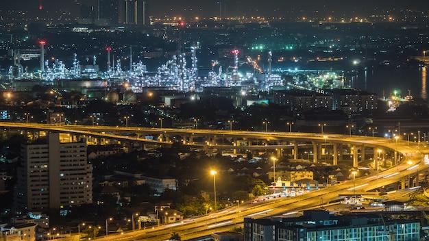 Ville de bangkok, thaïlande, montrant le trafic sur une autoroute et une raffinerie de pétrole la nuit Photo Premium