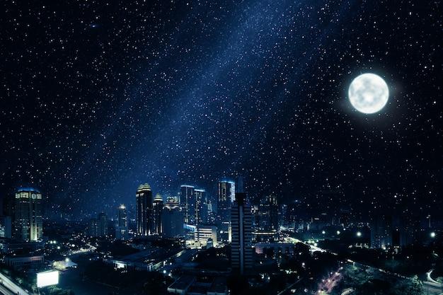 Ville rougeoyante avec lune brillante et nombreuses étoiles dans le ciel Photo Premium