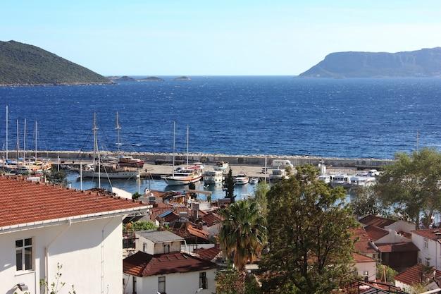 Villes méditerranéennes sur la plage aux toits de tuiles rouges. port de plaisance à kas, turquie Photo Premium
