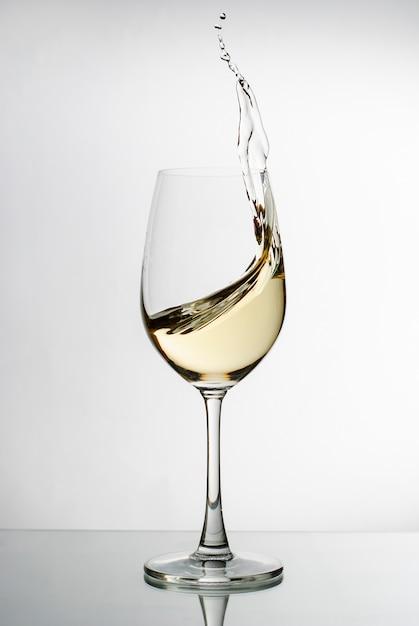 Vin blanc éclaboussant d'un verre à vin élégant Photo Premium