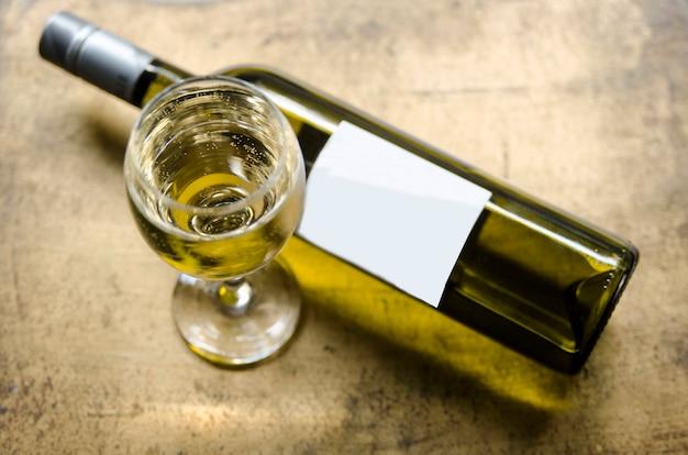 Vin blanc en verre et bouteille sur une table rustique dorée Photo Premium