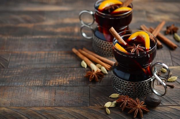 Vin chaud aux oranges et épices sur la vieille table en bois. Photo Premium
