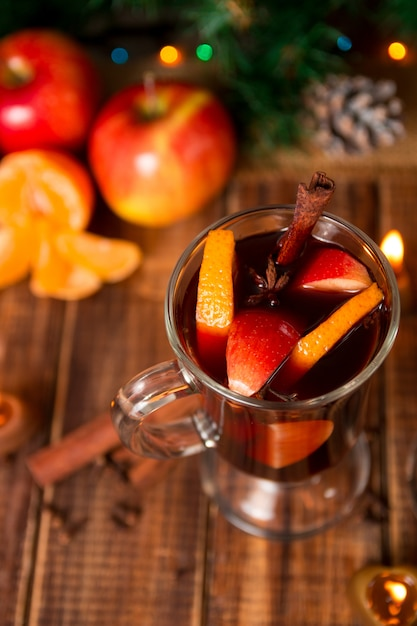 Vin chaud de noël avec des fruits et des épices sur une table en bois Photo Premium