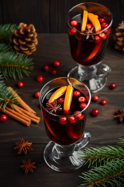 Vin chaud de noël à l'orange et aux canneberges. concept de vacances décoré de branches de sapin et d'épices. Photo Premium