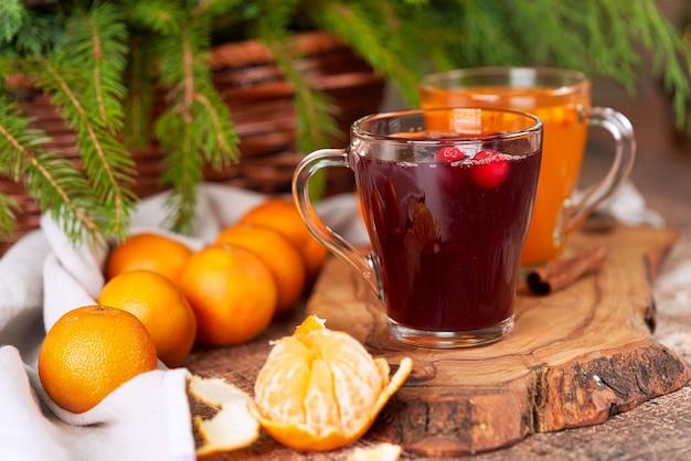Vin Chaud Rouge Et Jaune Dans Des Tasses En Verre Sur Une Table De Noël Avec Des Mandarines. Nouvel An Encore La Vie De Près Photo Premium