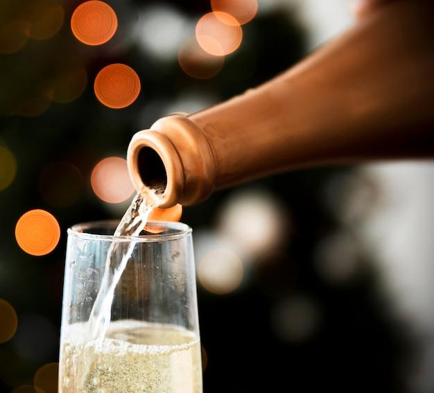 Vin mousseux versé dans un verre à la fête de noël Photo gratuit