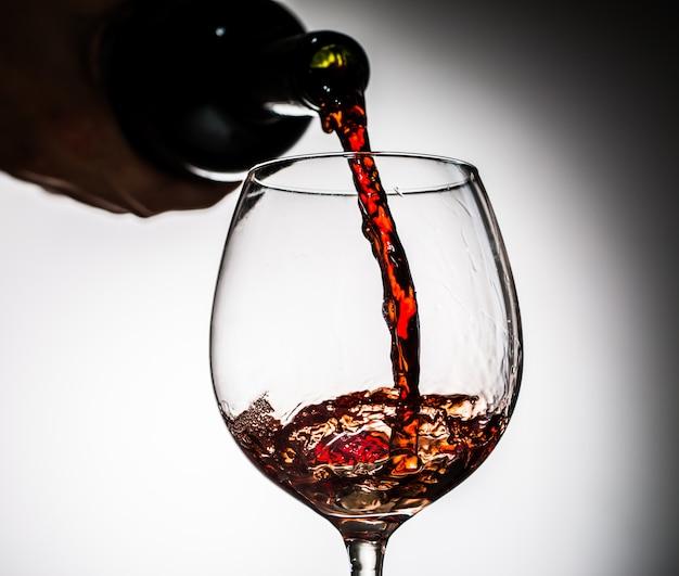 Vin de raisin versé de la bouteille dans un verre à vin en verre Photo Premium