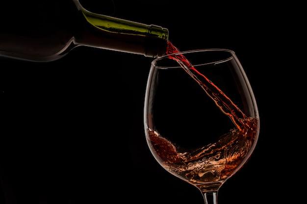 Vin de raisin versé dans un verre à vin sur fond noir Photo Premium