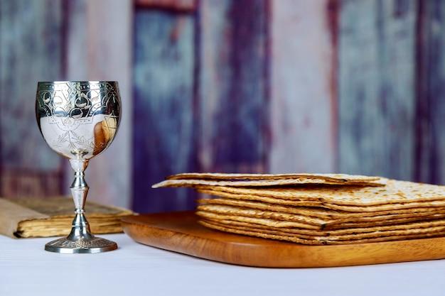 Vin rouge casher avec une assiette blanche de matzah ou matzo et une haggadah de pâque Photo Premium