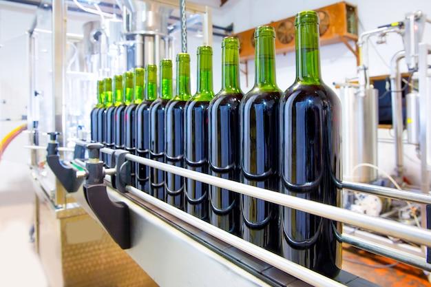 Vin rouge en machine d'embouteillage à la cave Photo Premium