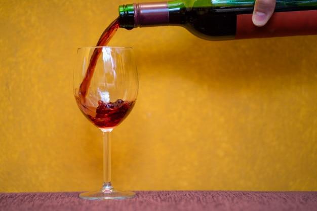 Vin rouge versé dans un verre sur fond jaune Photo Premium