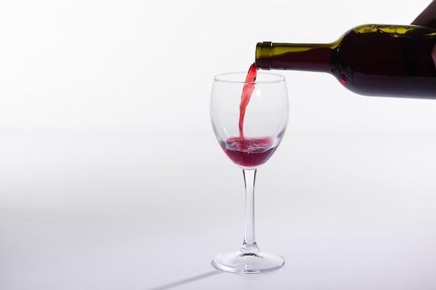 Vin Rouge, Verser Dans Le Verre De La Bouteille Sur Fond Blanc Avec Copie Espace Photo Premium