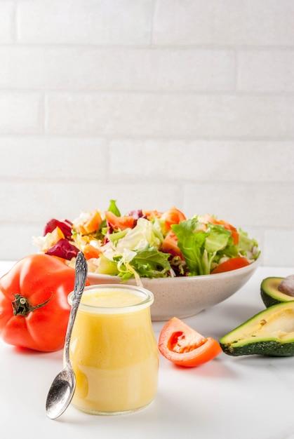 Vinaigrette à la moutarde au miel classique avec des légumes frais sur une table en marbre blanc Photo Premium