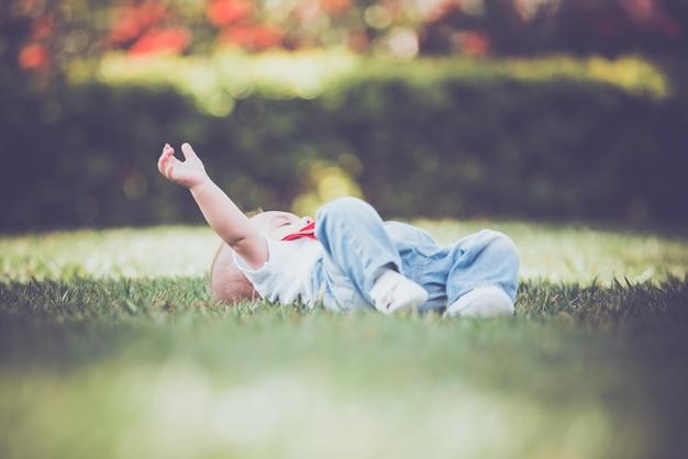 Vintage bébé garçon avec jarretelle rouge en plein air - couché sur l'herbe Photo Premium