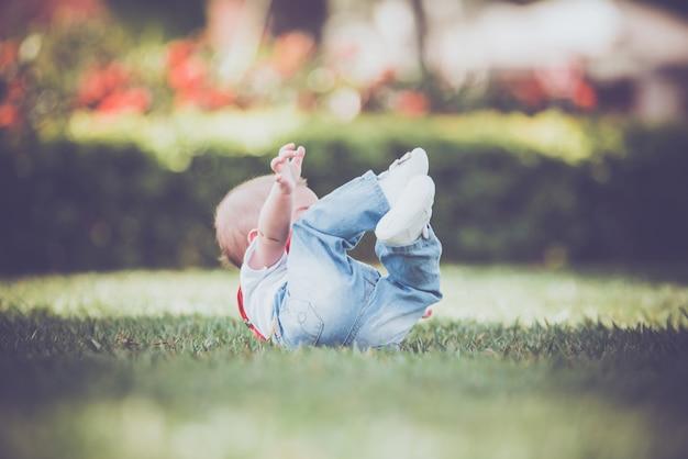 Vintage bébé garçon avec jarretelle rouge en plein air - tomber sur l'herbe Photo Premium