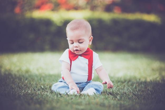 Vintage bébé garçon avec jarretelle rouge en plein air Photo Premium