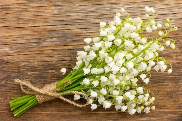Vintage bouquet de fleurs sauvages, les lys parfumés blancs de la vallée sur une vieille planche de bois closeup Photo Premium