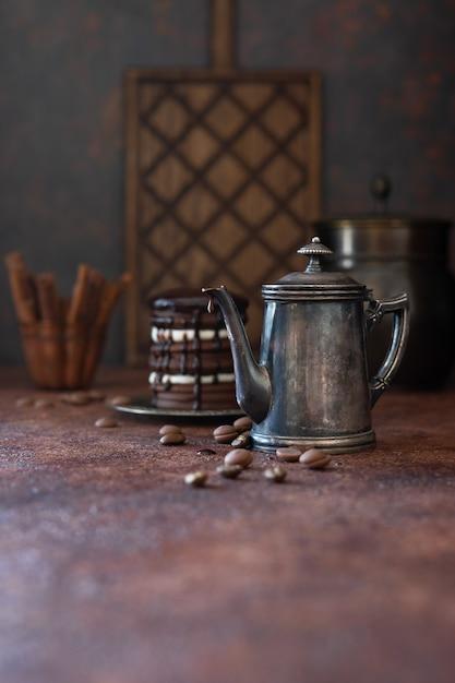 Vintage cafetière et gouttes de chocolat sur fond sombre Photo Premium