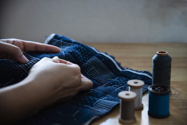 Vintage femme couture tissu à la main avec broderie mis sur la table en bois - personnes et concept de ménage bricolage à la main Photo gratuit