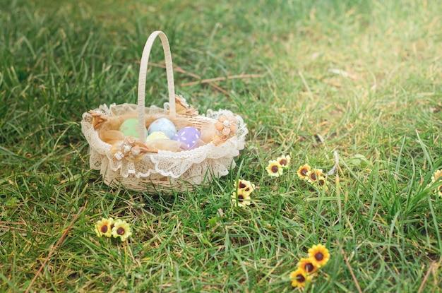 Vintage fond de pâques avec des oeufs décorés dans un panier sur l'herbe et des fleurs Photo Premium