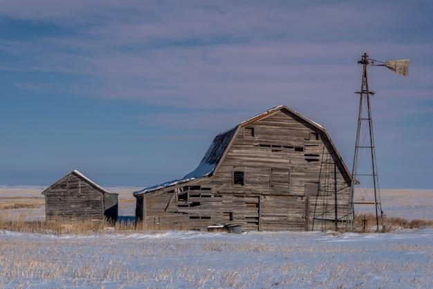 Vintage grange, bacs et moulin à vent entouré de neige sous un ciel de coucher de soleil rose en saskatchewan, canada Photo Premium
