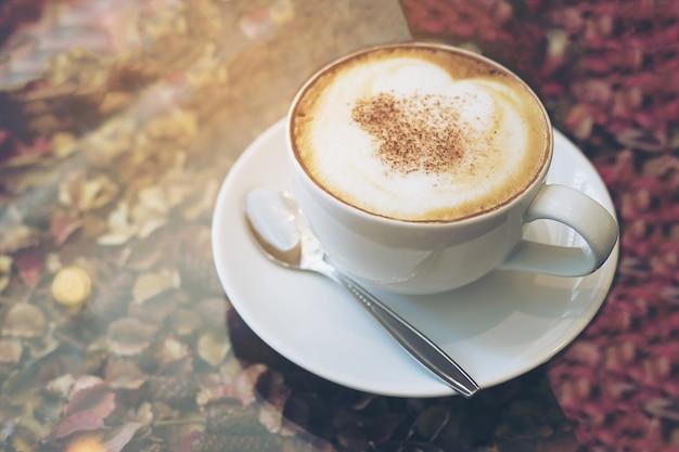 Vintage photo de tasse de café chaud sur la texture de pétales de fleurs séchées et le dessus de table en verre Photo gratuit