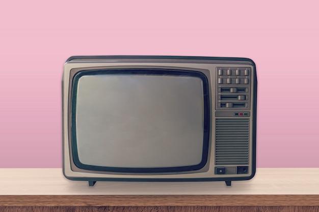Vintage tv box sur table en bois et fond de couleur rose pastel. Photo Premium