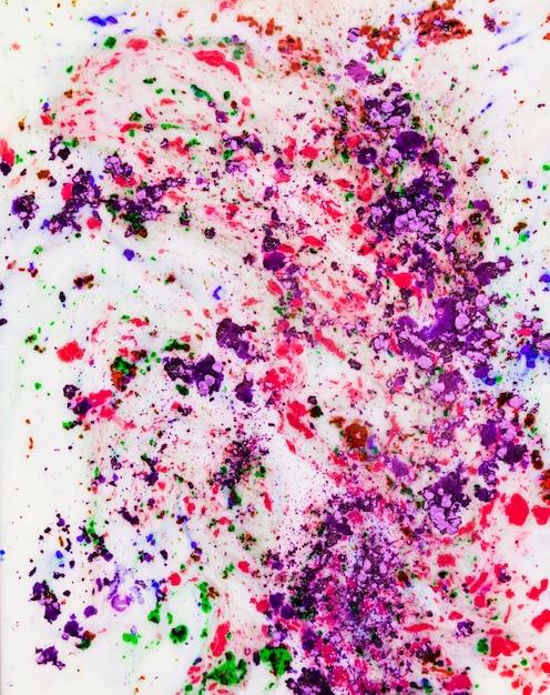 Violet; poudre de couleur holi rose et vert mélangée sur fond blanc Photo gratuit