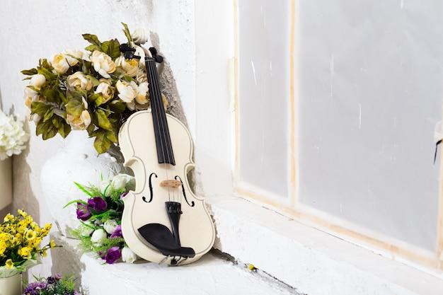 Violon blanc avec fleurs et salle blanche Photo Premium