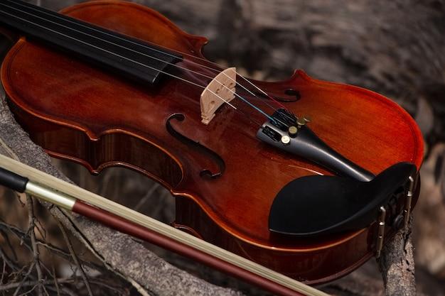 Le violon en bois et l'archet mis sur une planche de bois, lumière floue autour Photo Premium