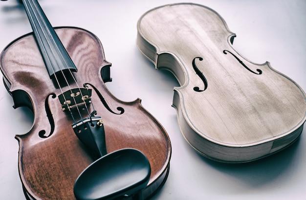Violon brut mis à côté du violon terminé, montre la face avant du violon Photo Premium