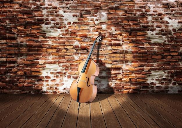Violoncelle sur scène appuyé contre un mur de briques rustiques Photo Premium