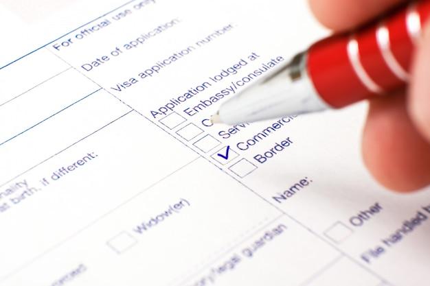 Visa schengen, questionnaire. la main avec un stylo remplissant un questionnaire. Photo Premium
