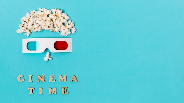 Visage anthropomorphe fait avec des pop-corn et des lunettes 3d sur le texte de l'heure du cinéma Photo gratuit