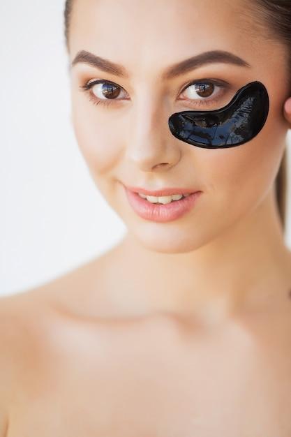 Visage beauté femme avec masque sous les yeux. belle femme avec des correctifs naturels de maquillage et de collagène noir sur une peau fraîche du visage Photo Premium