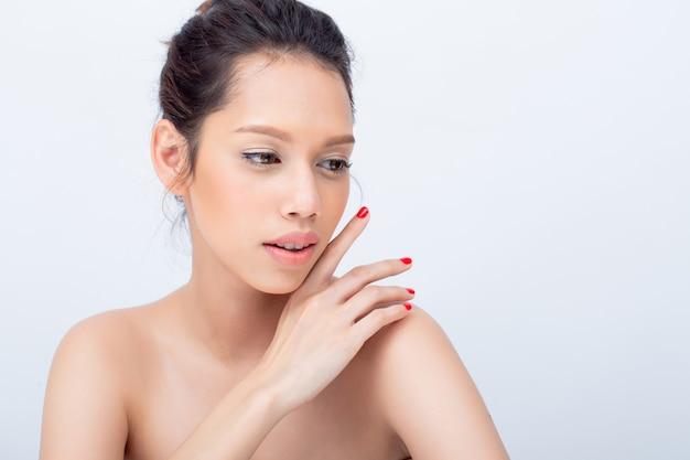 Visage beauté v-shape de mannequin asiatique jeune femme avec un maquillage naturel touche son visage Photo Premium