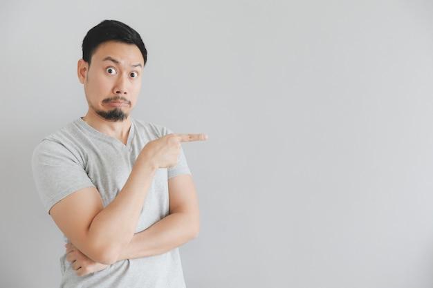 Visage choqué de l'homme en t-shirt gris avec la main pointent sur un espace vide. Photo Premium