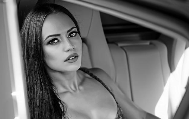 Visage De Femme Sexy Dans Une Voiture De Luxe. Portrait De Jeune Fille Sexy Glamour Fashion Aux Longs Cheveux Magnifiques Photo Premium