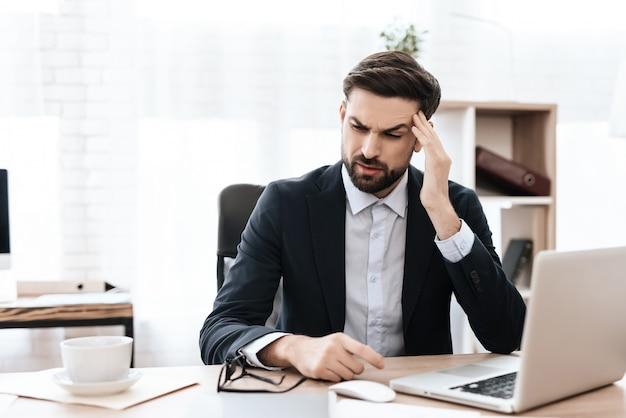 Le visage grimace de douleur. l'homme est assis au travail. Photo Premium