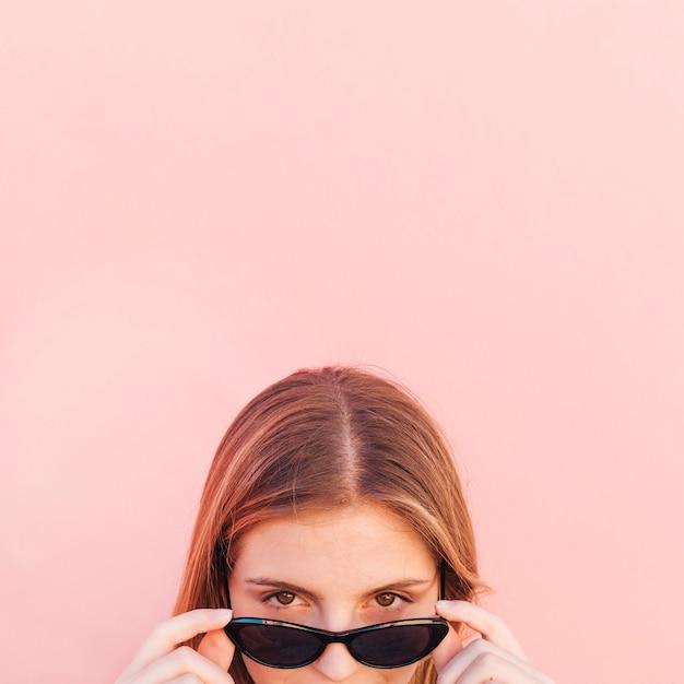 Visage de jeune femme furtivement à travers des lunettes de soleil noires sur fond rose Photo gratuit
