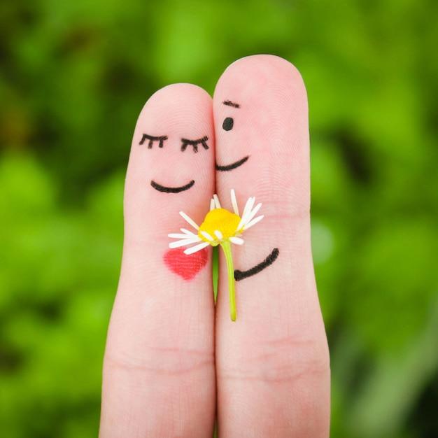 Visage peint sur les doigts. l'homme donne des fleurs à une femme. Photo Premium