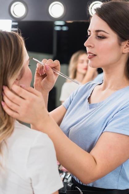 Visagiste maquillant les sourcils du client Photo gratuit