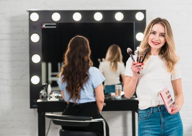 Visagiste tenant des pinceaux à maquillage et une palette d'ombres à paupières Photo gratuit