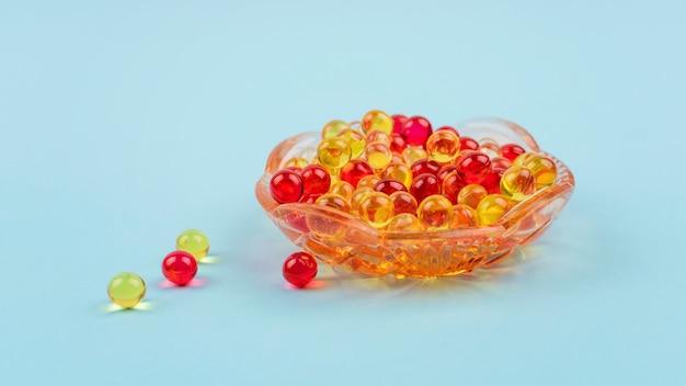 Vitamine a, e, d, oméga 3 jaune et rouge Photo Premium