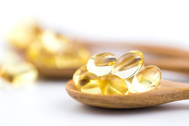 Vitamines saines sur une cuillère en bois avec un fond blanc. Photo Premium