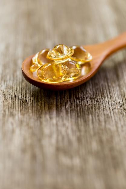 Vitamines saines sur une cuillère en bois. Photo Premium